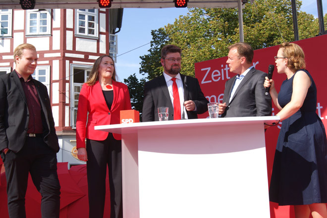 """Politikgrößen in der Mitte (Gabriele Andretta, Marcus Seidel, Thomas Oppermann), Erstwähler Julian Ehbrecht (links) verspricht unter Applaus, """"natürlich die SPD"""" zu wählen."""