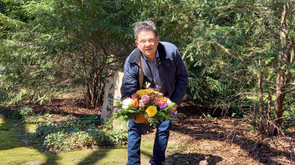 Dr. Andreas Philippi legt einen Blumenstrauß nieder